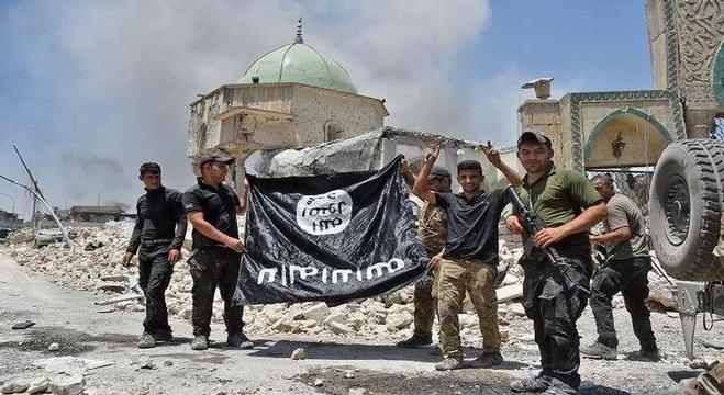 جنود عراقيون يحملون راية داعش بالمقلوب بعد تحرير مركز مدينة الموصل